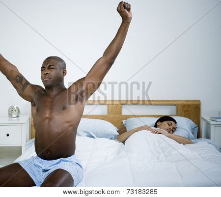 African man stretching on edge of bed