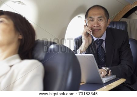 Asian businessman working on airplane