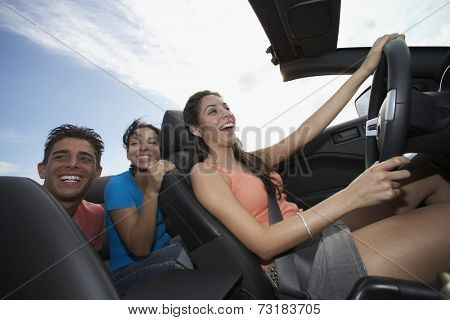 Multi-ethnic friends driving in convertible