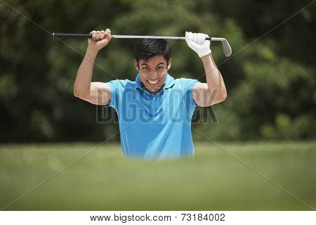 Frustrated Hispanic man holding golf club
