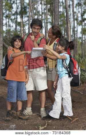 Hispanic family looking at map in woods