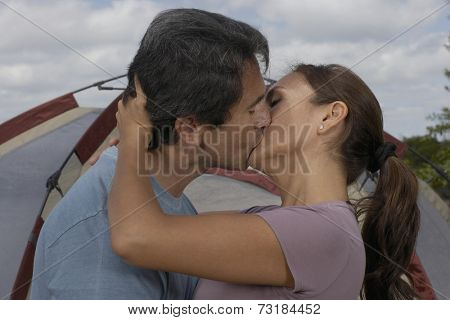 Hispanic couple kissing in front of tent