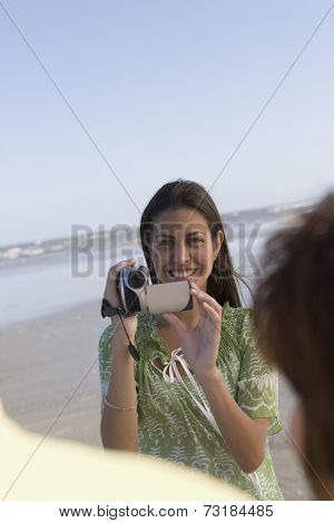 Hispanic girl video recording people at beach