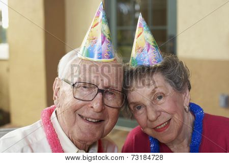Senior couple wearing party hats