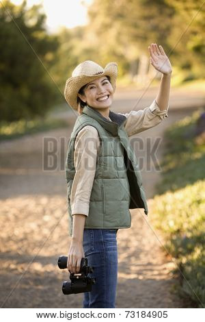 Asian woman holding binoculars and waving
