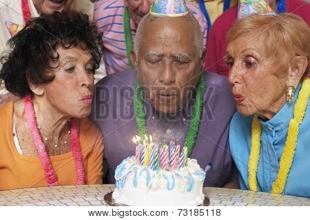 Senior Mixed Race man blowing out birthday candles