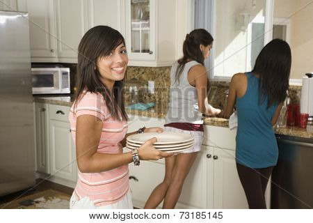 Hispanic teenaged girls washing dishes