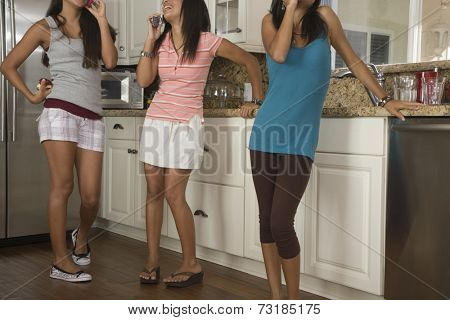 Hispanic teenaged girls in kitchen