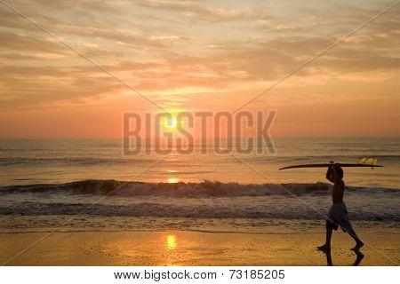 Asian boy carrying surfboard at beach