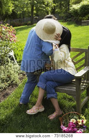 Hispanic couple hiding behind straw hat