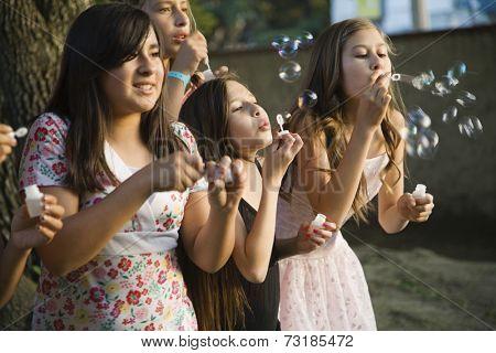 Hispanic girl blowing bubbles