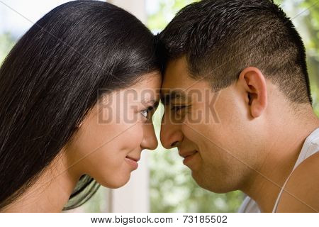 Multi-ethnic couple touching foreheads