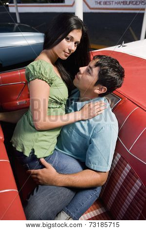 Multi-ethnic couple in back seat of convertible