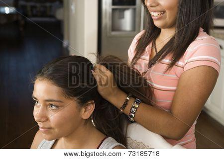 Hispanic girl fixing friend's hair