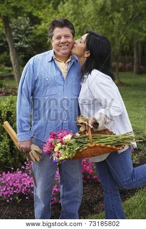 Hispanic woman kissing husband on cheek