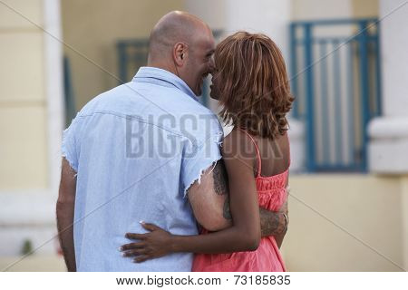 Rear view of multi-ethnic couple hugging