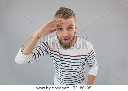 Portrait of trendy guy looking away, hand on forehead