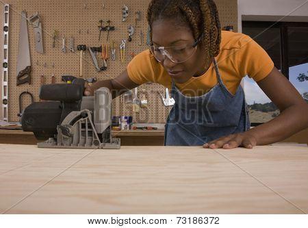 African American woman cutting wood