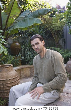 Hispanic man sitting in garden