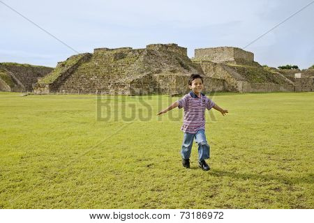 Hispanic boy running in front of ruins, Oaxaca, Mexico