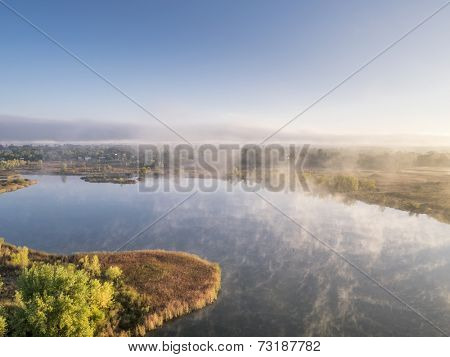 aerial view of a morning fog over lake, early fall scenery, Riverbend Ponds Natural Area, Fort Collins, Colorado, shot from low flying drone