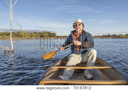 senior male enjoying morning sun on lake in a canoe, Riverbend Ponds Natural Area, Fort Collins, Colorado