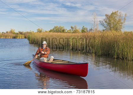 senior male paddler paddling a red canoe on a calm lake, Riverbend Ponds Natural Area, Fort Collins, Colorado