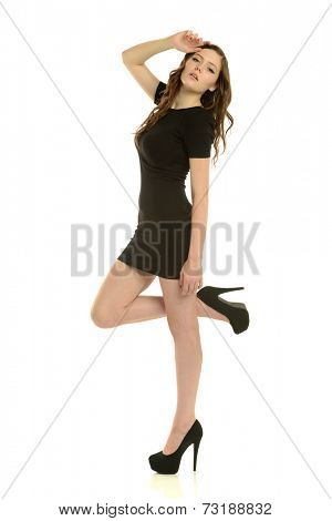 Young brunette woman wearing a short dress and heels isolated on a white background