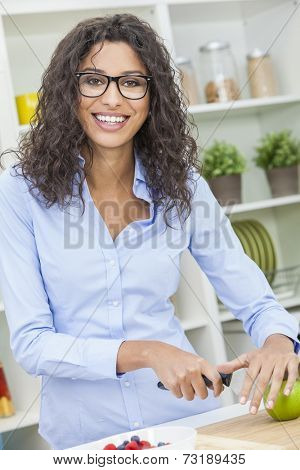 A beautiful happy young woman or girl wearing glasses cutting & preparing an apple for fresh fruit salad food in her kitchen at home