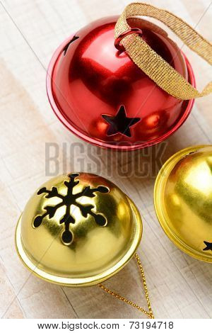 Closeup of three jingle bells on a white wood table. Two gold bells and one red in vertical format with shallow depth of field, focus on the red and large bell.