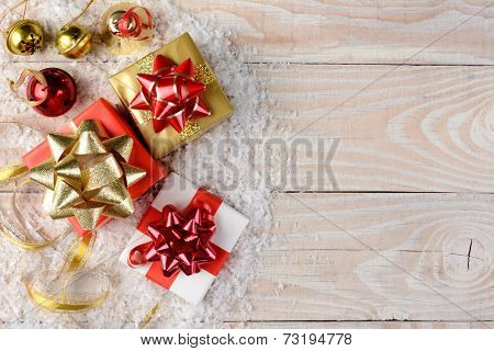 Christmas presents, bells and ribbon with artificial snow on a rustic wooden table. Horizontal format with copy space.