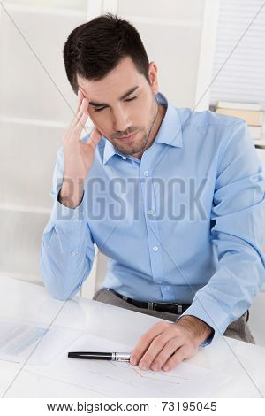 Overstrained and overworked businessman with headache: Portrait sitting in his office.