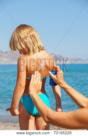 Mother applys sunblock cream on daughter's back