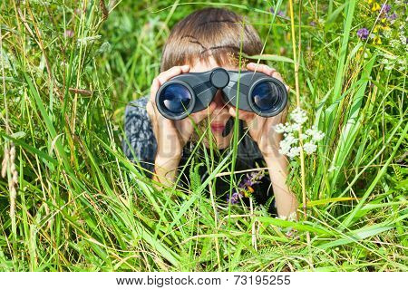 Boy hiding in grass looking through binoculars outdoor