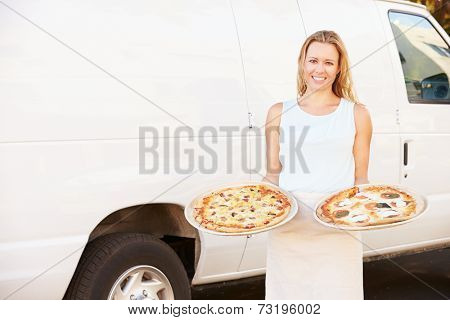 Woman Delivering Pizza Standing In Front Of Van