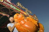 image of stuffed animals  - Young woman holding a stuffed animal at a carnival - JPG