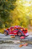 stock photo of logging truck  - Vintage red truck carrying autumn leaves  - JPG
