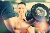 stock photo of lifting weight  - Man or Bodybuilder with his personal fitness trainer in the gym exercising sport with dumbbells - JPG