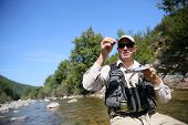 pic of fly rod  - Flyfisherman choosing artificial fly for fishing rod - JPG