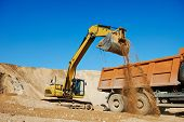 stock photo of risen  - wheel loader excavator machine loading dumper truck at sand quarry - JPG