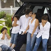 stock photo of pre-adolescent child  - Parents kissing while children cover their eyes - JPG