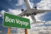 picture of bon voyage  - Bon Voyage Green Road Sign and Airplane Above with Dramatic Blue Sky and Clouds - JPG