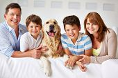 foto of thoroughbred  - Smiling family with thoroughbred dog looking at camera - JPG