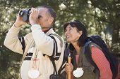 image of binoculars  - Senior couple looking through binoculars in woods - JPG