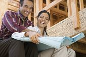 picture of blueprints  - Hispanic couple looking at blueprints at construction site - JPG