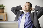 stock photo of chums  - Indian businessman smiling with hands behind head - JPG