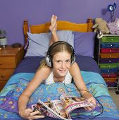 stock photo of pre-adolescent girl  - Teenaged girl reading in bedroom - JPG
