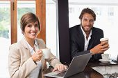 stock photo of half-dressed  - Business people smiling at the camera at the coffee shop - JPG