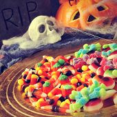 stock photo of cobweb  - a pile of different Halloween candies with scary ornaments in the background - JPG
