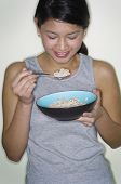 image of early 20s  - Portrait of Asian woman eating cereal - JPG
